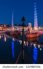 Footbridge at night, over water at a harbour and marina in Torquay, Devon, UK. A bluehour photo of Torquay with reflections from the lights shimmering in the water.