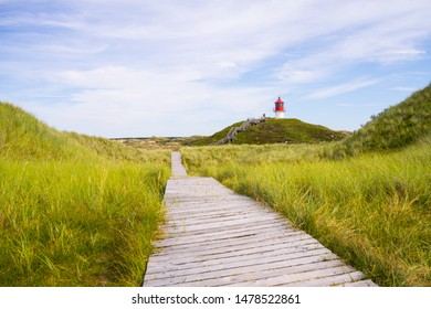 Footbridge path, lighthouse, dunes and blue sky on Amrum