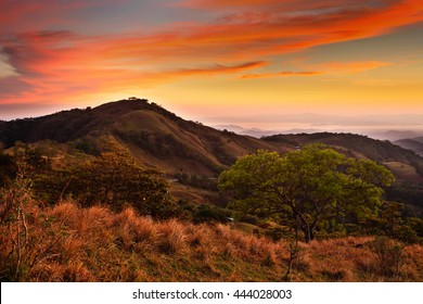 Foothills of Monteverde Cloud Forest Reserve, Costa Rica. Tropical mountains after sunset. Hills with beautiful orange sky with cloud.