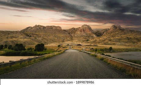 Foothills of the Rocky Mountains and glimpse of Shoshone river under beautiful sky at dusk as viewed from road in Cody, Wyoming, USA.