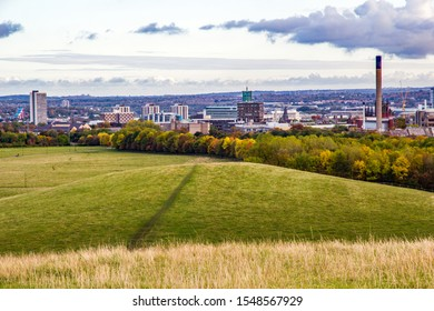 A footpath across the fields leads to Newcastle Upon Tynes skyline or cityscape seen from a hill in town moor park in autumn during golden hour before sunset