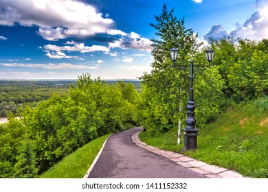 Footpath around the monument in the shade of green trees with lush foliage and a cast-iron black street lamp against a blue sky with white clouds. Park of Salavat Yulayev, Ufa, Bashkortostan, Russia.