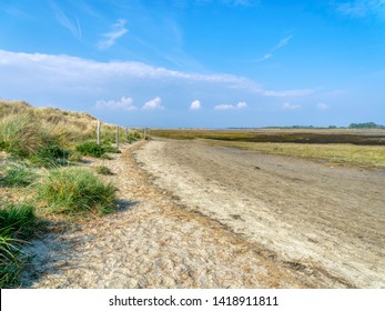 A footpath at the bottom of sand dunes leading around West Wittering saltmarsh