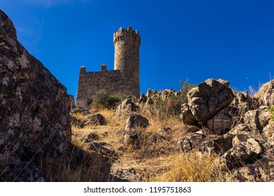 Footpath heading upwards to a medieval watchtower under a blue sky (Torrelodones, Spain)