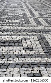 A footpath of light and dark grey cobblestones form a geometric pattern.