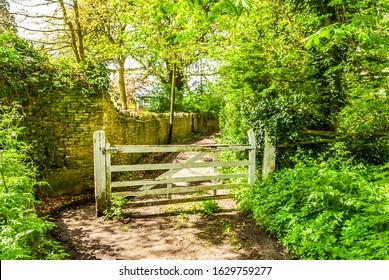 Footpath next to a wall with large white five bar gate. Chipping Norton, Oxfordshire. England.
