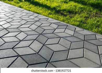 The footpath in the park is paved with diamond shaped concrete tiles.