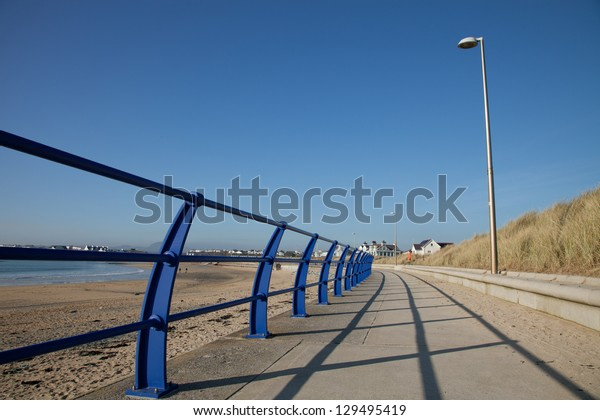 Footpath and railings with a lampost skirting the edge of a beach, Trearddur bay, Anglesey, Wales, UK.