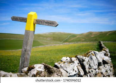 A footpath sign painted yellow in limestone countryside backed by green meadows and a blue sky on a tummy day.