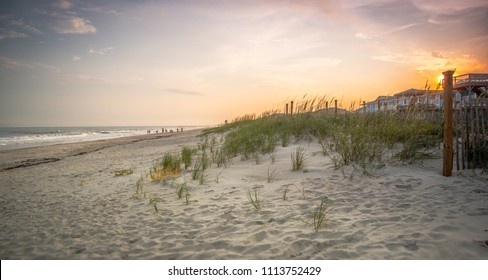 A footpath through the dunes leads to the ocean shore at sunset/sunrise.