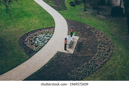 A footpath walkway in the park, the footpath passes by the bench, sidewalk, sideway - Shutterstock ID 1969572439