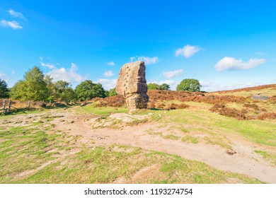 A footpath winds around the ancient Cork Stone under a bright summer sky on Stanton Moor in the Derbyshire Dales
