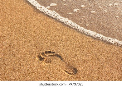 footprint in golden sand on the shore of the sea