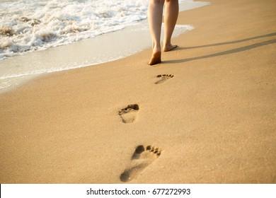 Huella en la playa con fondo de olas.