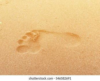 Footprint on the beach with warm light in the morning of winter season represent traveling in the high season of Thailand