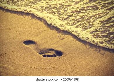 Footprint on sand beach along the edge of sea, vintage retro style.