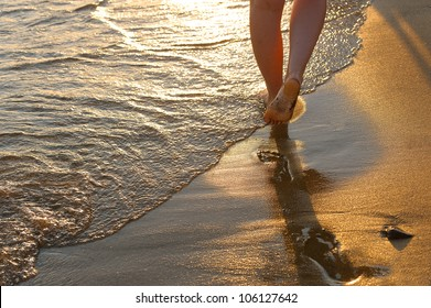 footprint on sand. Sunset illumination, a fragment of female feet