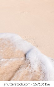 Footprint in the sand erased by a wave.
