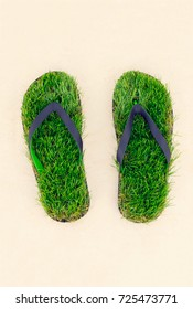 Footprint, sandals made of green artifitial grass on marble background. Save the nature, environment, ecology concept
