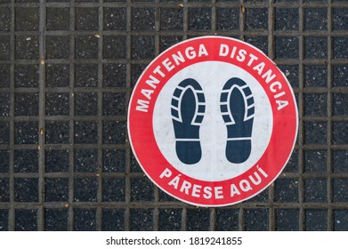Footprint sign for stand at a distance, in the street of Buenos Aires, Argentina. Social distance word tag poster. Instruction against propagation. New normal. Social distancing during covid19