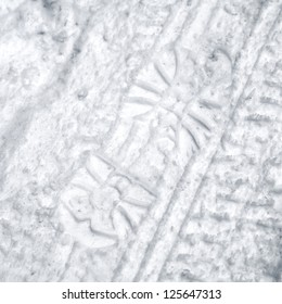 Footprint and tire tracks in the snow on the roadside