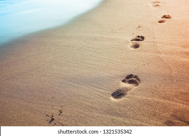 Footprints of bare feet on wet sand of the beach, vintage toned photo background