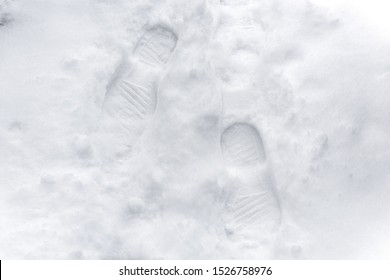 Footprints fresh snow. Footprints in the white snow, snowdrift. White snow with traces of man. Top view of human footprints on white snow.
