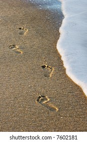 Footprints on the beach being swept away