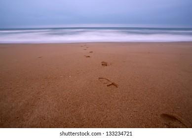 Footprints on the beach towards the ocean