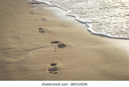 Footprints on golden sand, sunset and waves on the beach.