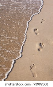 footprints on sand beach along the edge of sea