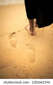 Footprints on sand beach from barefoot young woman in black dress with sea