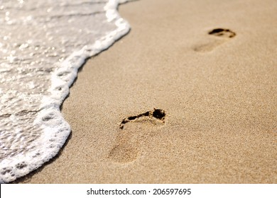 footprints on the sand of the beach at dawn
