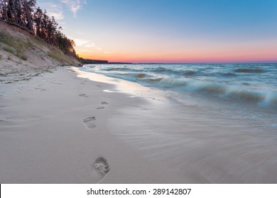 Footprints on the sand at empty sunset beach.