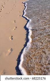 Footprints on sand. Prints of feet on beach sand are washed off by the sea in an instant.