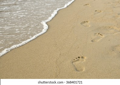footprints on the sand and sea wave