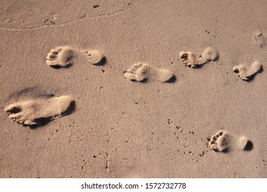 Footprints on the sand washed by the Sardinian sea