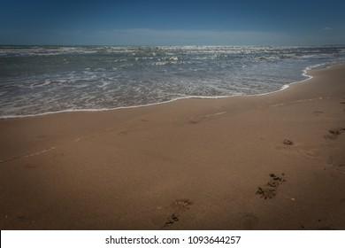 Footprints on sandy beach beaten by waves, Bibione, Veneto, Italy