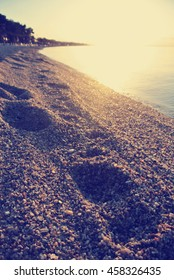 Footprints on the sandy beach at sunset, with sun and sea in the background. Image filtered in faded, retro, Instagram style with soft focus; nostalgic, vintage concept of summer holidays and travel.