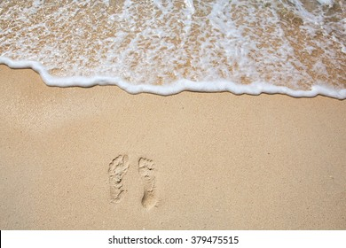Footprints on sea shore. Sea water wave. Beach Vacation