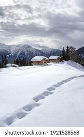 Schneefußspuren mit Schweizer Alpen Winterlandschaft und Chalets auf dem Hintergrund