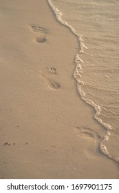 Footprints on a wet beach sand washed by wave