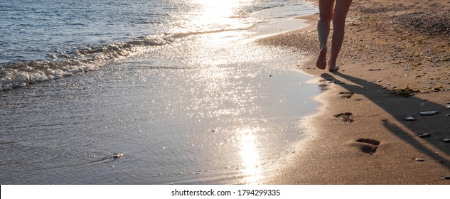 footprints on wet sand,  female feet walking at the water's edge by sea. natural background, copy space, banner