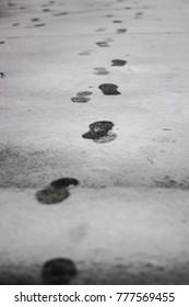 Footprints on wet snow leaving afar on the empty road in winter