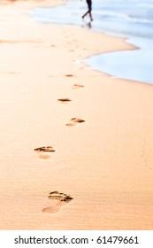 Footprints on yellow sand on the seashore
