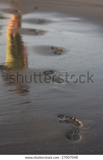 footprints and reflection on the wet sand