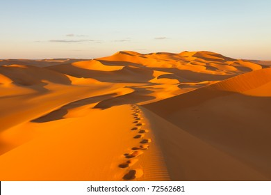 Footprints in the sand dunes at sunset - Murzuq Desert, Sahara, Libya