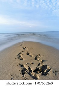 Footprints in the sand leading to ocean beach water during low tide. Sandbar at an Atlantic Canadian beach with rippling tide trickling in with beautiful blue sky overhead. Beach walk