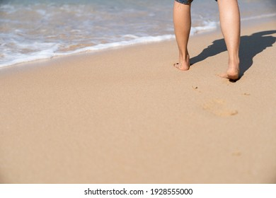 Footprints in the sand on the beach. Woman walking to the sea.