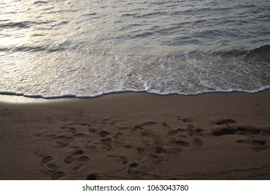 Footprints in the sand, sea, sunrise